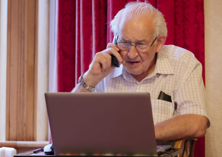 Elderly man using laptop computer and talking on phone